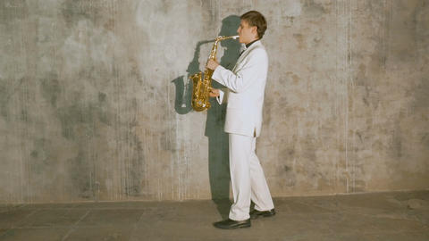 A musician in a white suit plays the saxophone Footage