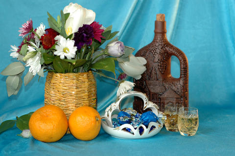 A bouquet of flowers, oranges, a bottle of wine, glasses, a vase Fotografía