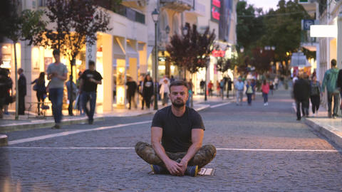 Timelapse of man sitting on crowded evening street while a blur of fast moving Footage