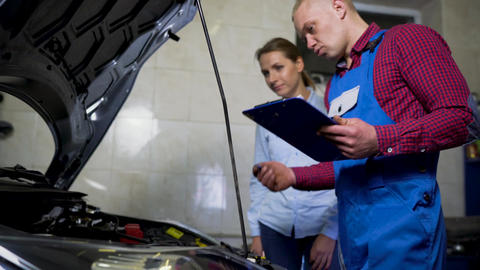 Car service, repair, maintenance and people concept - mechanic checks the Footage