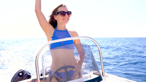 Summer vacation - young girl driving a motor boat on the sea. Slow motion Live Action