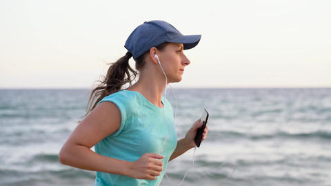 Athletic woman running along the beach Footage