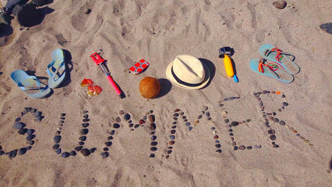 Word summer from sea stones laid out on sand GIF