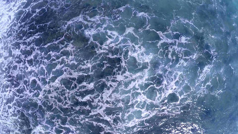 Aerial drone footage of huge waves rushing shore GIF