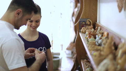 guy and a girl are looking at clay toys and souvenirs in an art workshop Footage