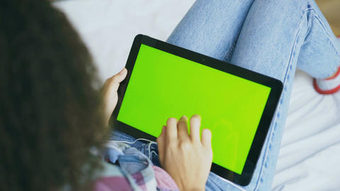 Back view of curly woman at home using electronic tablet with green screen Footage