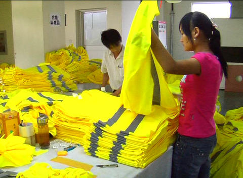 Factory workers folding jackets Stock Video Footage