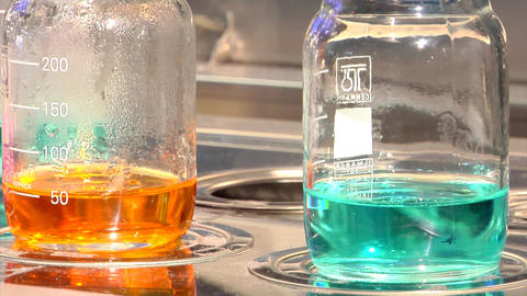 Laboratory beakers with different coloured chemicals Stock Video Footage