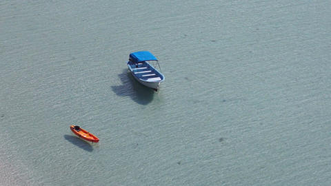 Kayak and a Boat Along the Ocean Beach Stock Video Footage