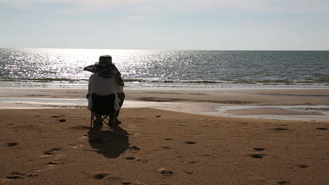 Senior man sitting at beach Stock Video Footage