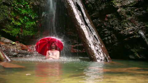 Man with umbrella at waterfall Stock Video Footage