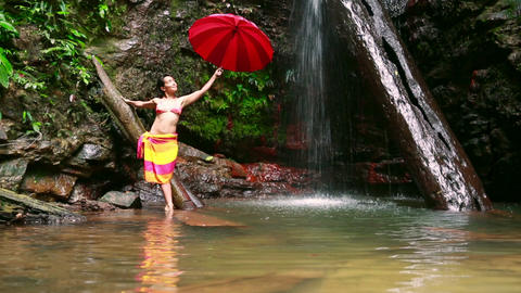 Girl with umbrella at waterfall Stock Video Footage