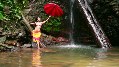 Girl with umbrella at waterfall Footage
