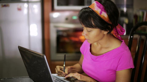 woman writing recipe from internet Stock Video Footage