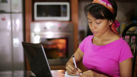 woman writing recipe from internet Footage