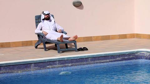 arabian talking phone at pool Stock Video Footage