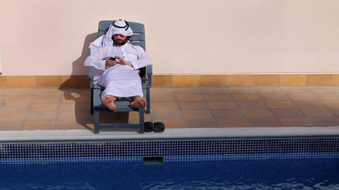 arabian using phone at pool Stock Video Footage