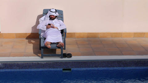 arabian using phone at pool Footage