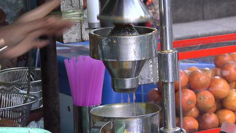 The squeezing of Fresh Thai Orange Juice from a Sidewalk Vendor, Bangkok Footage