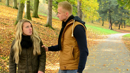 concept - domestic violence - unhappy couple in autumn park - man grasps woman's Footage