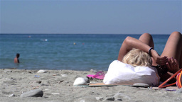 People sitting on the beach by the sea while others take a bath in blue water 2 Footage