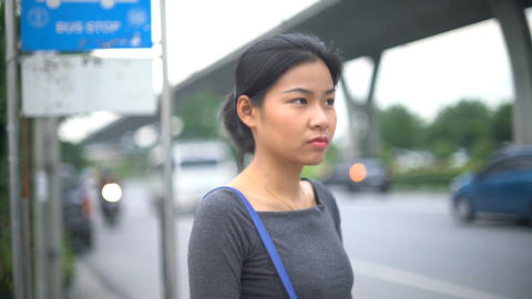 Young Asian Woman stands at bus stop and explaining the way Footage