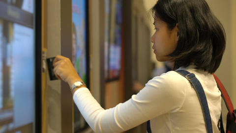 Asian Girl buying movie tickets using self-service machine Live Action