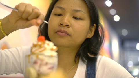 Young Asian Woman eating cherry from top of ice cream Footage