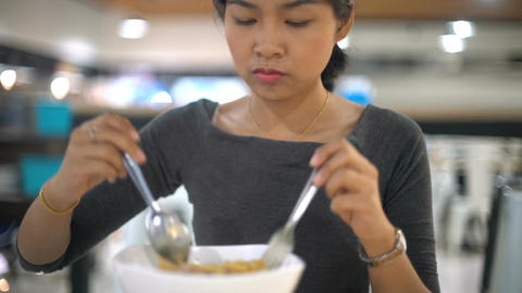 Portrait of Young Asian Lady eating noodle soup in foodcourt Live Action