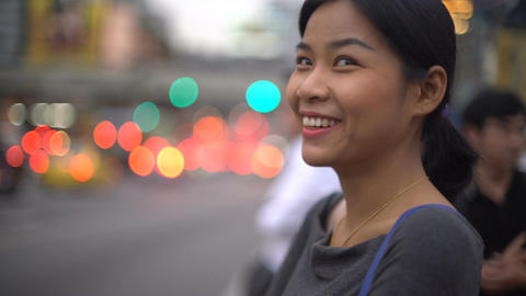 Portrait of pretty Asian Girl waits for green light near road Footage
