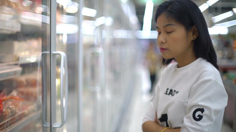Young Asian Woman selecting products in grocery store Footage