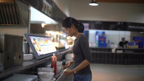 Young Asian Lady is adding spices into dish in food court Footage