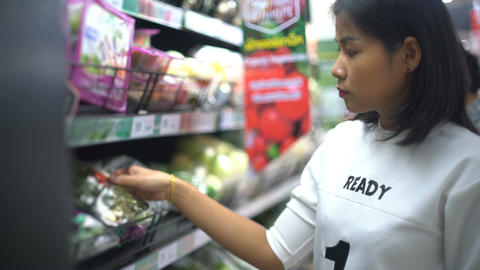 Young Asian Woman buying vegetables in supermarket Live Action