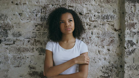 Thoughtful young mixed race girl thinking about solving problem on brick wall Live Action