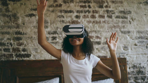 Curly african american woman getting experience using VR 360 headset glasses of Footage