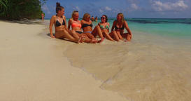 v12692 sunbathing group of young beautiful girls on white sand beach in aqua Live Action
