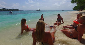v12706 sunbathing group of young beautiful girls on white sand beach in aqua Live Action