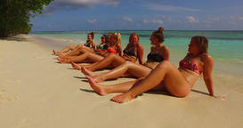 v12726 sunbathing group of young beautiful girls on white sand beach in aqua Live Action