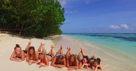 v12740 sunbathing group of young beautiful girls on white sand beach in aqua Live Action