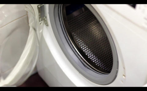 The hand opens the door of the washing machine and loads the clothes Footage