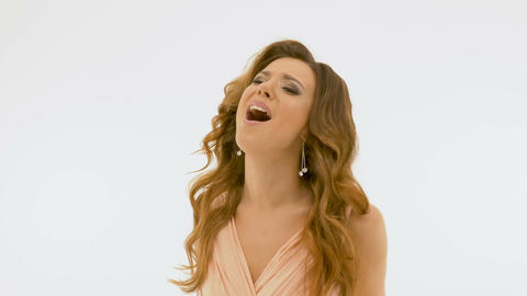 Beautiful woman with long hair singing. White background Footage