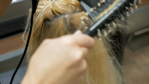 A stylist barber combs her hair to a blonde woman Archivo