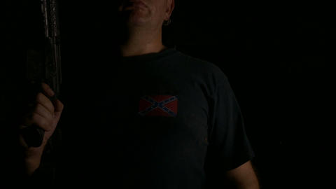 Anonymous man carrying assault rifle wearing dixie flag t-shirt Live Action