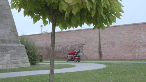 Tourists strolling with electric vehicles through the defensive ditches of an Live Action