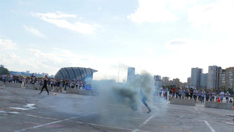 People Entertain Audience Dancing with Fireballs on Square Live Action