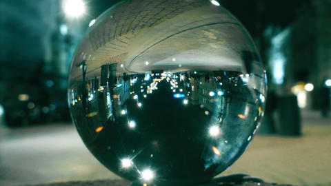 Night city street traffic reflecting upside down in the glass ball Footage