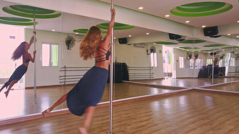 Blonde Girl Swings on Pole to Music in Dance Hall Live Action