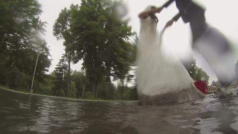 wedding in the rain. bride and groom jumping in the puddle in the rain Footage