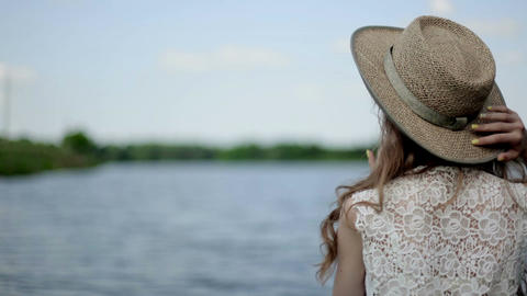 girl turns her head. beautiful girl by the lake. girl in a hat near a lake Live Action