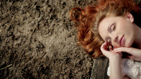 girl with luxurious red hair lies on the ground Image